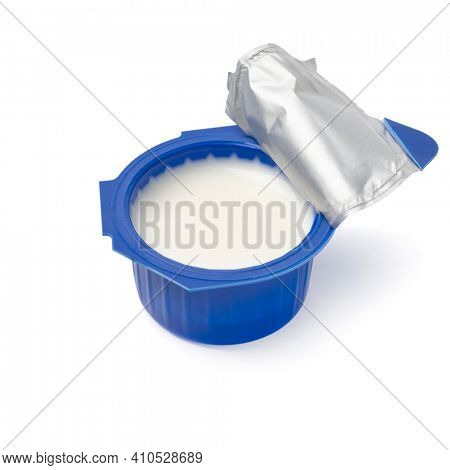 Single open blue plastic cup of coffee creamer close up isolated on white background