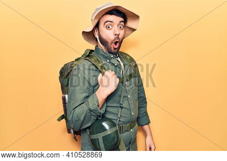 Young hispanic man wearing explorer hat and bakcpack scared and amazed with open mouth for surprise, disbelief face