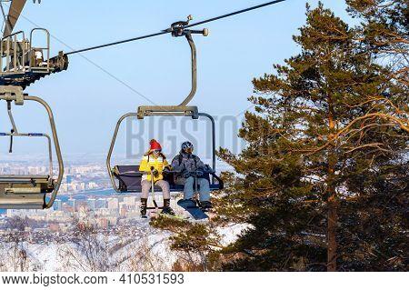Krasnoyarsk, Russia - February 20, 2021: Skier And Snowboarder On Chairlift And Ski Slope Resort Of
