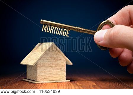 Key To Your Own Home Is To Get Mortgage. Wooden Model Of House And Key With Text Mortgage In Hand.
