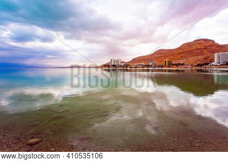 Low winter clouds are reflected in the green water. The smooth surface of the salty sea reflects the sky and clouds. Israel, legendary Dead Sea