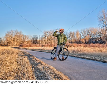 hydration break during winter or fall commuting on a bike trail - Poudre River Trail in northern Colorado