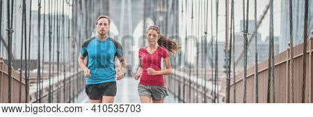 New York city runners athletes training for run marathon on Brooklyn Bridge banner. Fit active interracial couple on outdoor running exercise in raining day. Summer rain. Asian woman, Caucasian man.