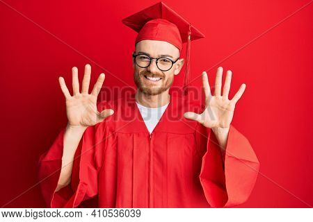 Young redhead man wearing red graduation cap and ceremony robe showing and pointing up with fingers number ten while smiling confident and happy.
