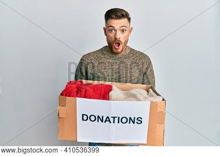 Young redhead man volunteer holding donations box afraid and shocked with surprise and amazed expression, fear and excited face.