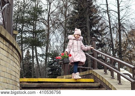 A Girl Of Eight Years Old In A Light Jacket And Hat With A Basket Of Scarlet Tulips Goes Down The St
