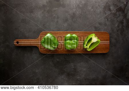 Sweetn Green Peppers On Wooden Cutting Board On Black And Dark Grey Background. Green Pepper Sliced