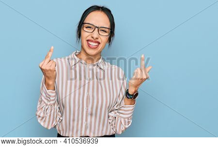 Young hispanic girl wearing casual clothes and glasses showing middle finger doing fuck you bad expression, provocation and rude attitude. screaming excited