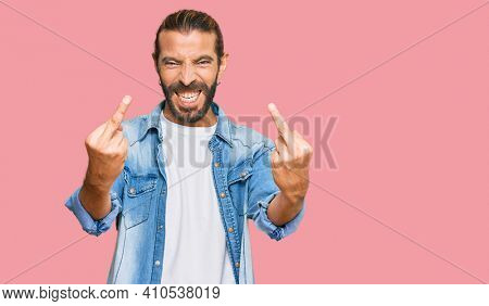 Attractive man with long hair and beard wearing casual denim jacket showing middle finger doing fuck you bad expression, provocation and rude attitude. screaming excited