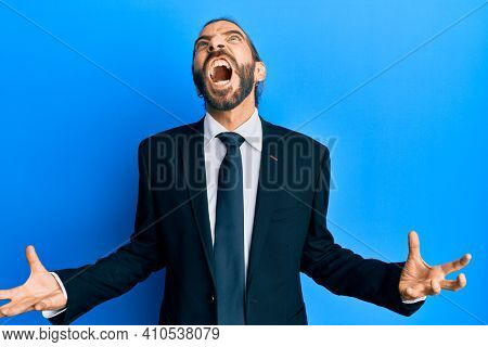 Attractive man with long hair and beard wearing business suit and tie crazy and mad shouting and yelling with aggressive expression and arms raised. frustration concept.