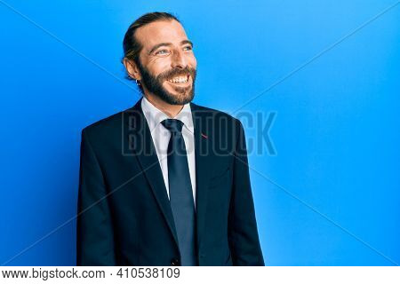 Attractive man with long hair and beard wearing business suit and tie looking away to side with smile on face, natural expression. laughing confident.