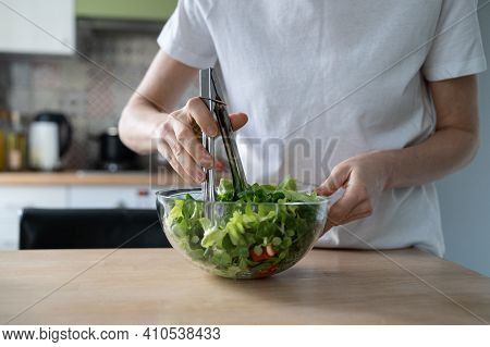 Close Up Of Woman Cooking Vegetable Salad At Home Kitchen. Female Hands Stirs Vegetarian Salad Of Fr