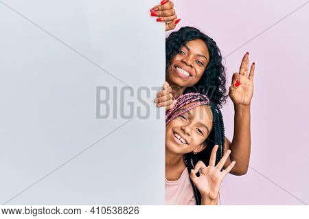 Beautiful african american mother and daughter holding blank empty banner doing ok sign with fingers, smiling friendly gesturing excellent symbol