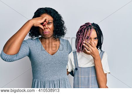 Beautiful african american mother and daughter wearing casual clothes and hugging smelling something stinky and disgusting, intolerable smell, holding breath with fingers on nose. bad smell