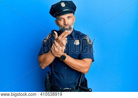 Middle age handsome man wearing police uniform holding symbolic gun with hand gesture, playing killing shooting weapons, angry face