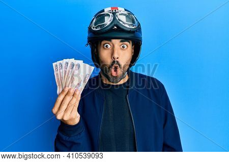 Young hispanic man wearing motorcycle helmet holding russian ruble scared and amazed with open mouth for surprise, disbelief face
