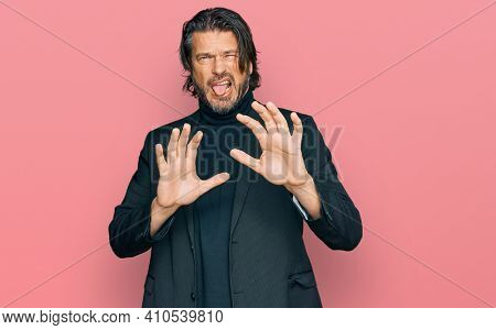 Middle age handsome man wearing business clothes disgusted expression, displeased and fearful doing disgust face because aversion reaction. with hands raised