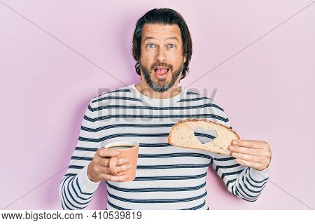 Middle age caucasian man holding bread loaf with heart shape drinking coffee afraid and shocked with surprise and amazed expression, fear and excited face.