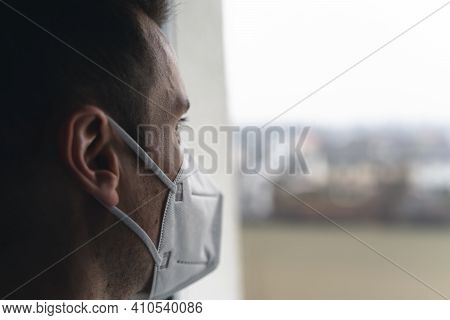 Close Up Of A Man Looking Out Of A Window While Wearing A Medical Ffp2 Protective Mask. Corona Virus