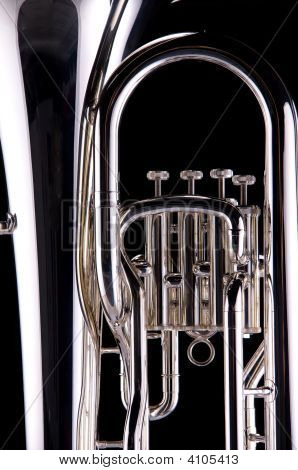 A silver tuba euphonium isolated against a black background in the vertical format. poster