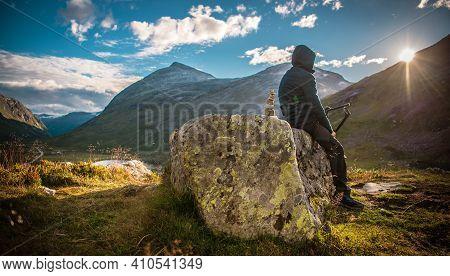 Male Alpine Hiker Taking Rest To Watch Scenic Sunset. Mountain Trail Recreation. Norwegian Landscape