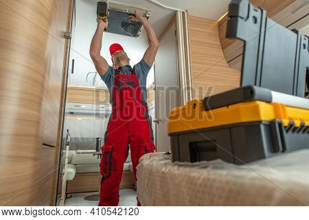 Rv Industry Caucasian Technician In His 40s Repairing Travel Trailer Ceiling Mounted Air Condition U
