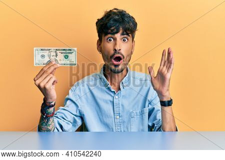 Young hispanic man holding  20 dollar banknote scared and amazed with open mouth for surprise, disbelief face