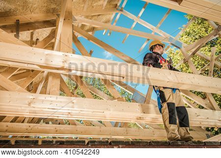 Skeleton Wood Frame Of House Building. Caucasian Contractor Worker On The Attic Frame. Industrial Th