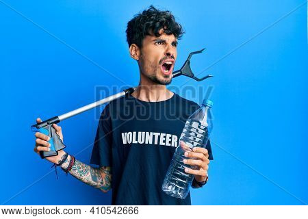 Young hispanic man holding plastic bottle and litter picker to recycle angry and mad screaming frustrated and furious, shouting with anger. rage and aggressive concept.