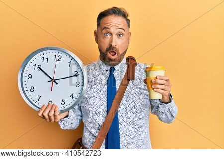 Handsome middle age business man drinking a cup of coffee and holding big clock afraid and shocked with surprise and amazed expression, fear and excited face.