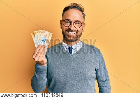 Handsome middle age man holding swiss franc banknotes looking positive and happy standing and smiling with a confident smile showing teeth