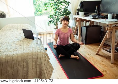 A Woman Sitting On A Mat In Front Of Bed While Doing Yoga Position In Bedroom. Relaxation Yoga Pract