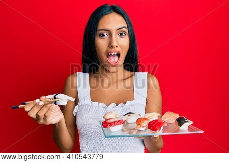 Young brunette woman eating butterfish sushi using chopsticks celebrating crazy and amazed for success with open eyes screaming excited.