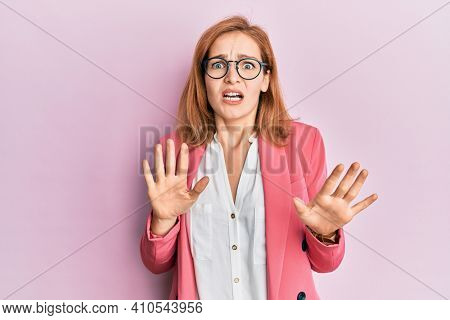 Young caucasian woman wearing business style and glasses afraid and terrified with fear expression stop gesture with hands, shouting in shock. panic concept.