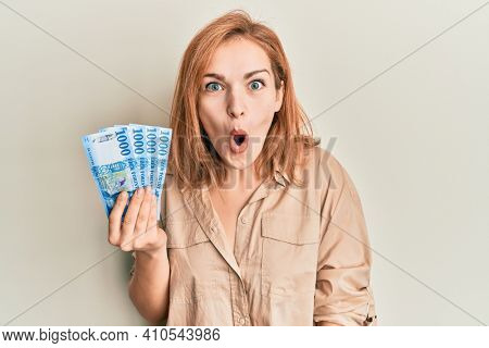 Young caucasian woman holding hungarian forint banknotes scared and amazed with open mouth for surprise, disbelief face