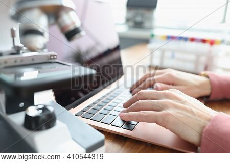 Female Hands Are Working On Laptop Next To Microscope. New Developments In The Field Of Chemistry Co