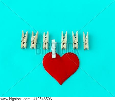 Love Symbol, Heart With A White Clothespin And Other Clothespins On A Turquoise Background