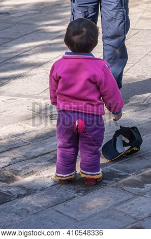 Beijing, China - April 29, 2010: Boy Toddler In Pink Vest And Purple Special Pants With Slit In Back