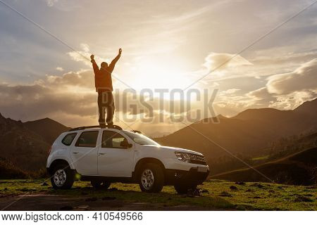 Person With Arms Raised And On The Roof Of His Off-road Car Watching The Sunset On The Mountain Afte