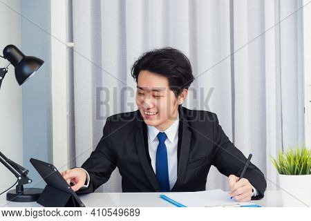 Work From Home, Asian Young Businessman Video Conference Call Or Facetime He Smiling Looking To Tabl
