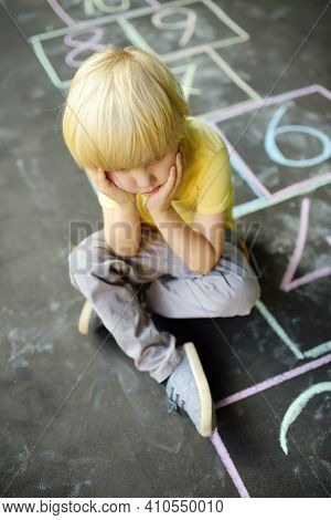 A Sad Little Boy Sitting On The Asphalt With Classics Painted On It. The Child Misses Friends During