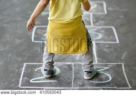 Little Boy's Jump On Hop Scotch Drawn On Asphalt. Child Playing Hopscotch Game On Playground Outdoor