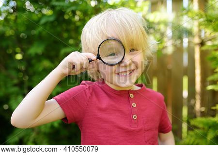 Little Boy Playing With Magnifying Glass. Little Boy Carefully Looking At You With Magnifier. Summer