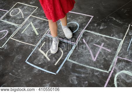 Closeup Of Little Girl's Legs And Hop Scotch Drawn On Asphalt. Child Playing Hopscotch Game On Playg