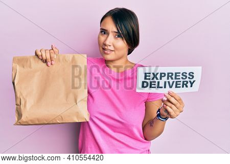 Beautiful young woman with short hair holding paper pag with express delivery text clueless and confused expression. doubt concept.