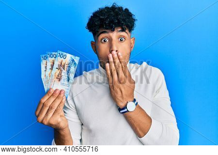 Young arab handsome man holding 100 swiss franc banknotes covering mouth with hand, shocked and afraid for mistake. surprised expression