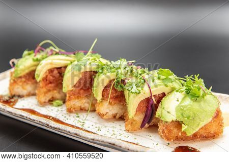 Crispy Rice Pieces Topped With Spicy Tuna And Avocado Drizzled With Spicy Mayo And Unagi Sauce.