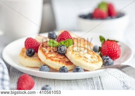 Close Up Of Cottage Cheese Pancakes With Fresh Berries On White Wooden Table. Curd Fritters With Ber