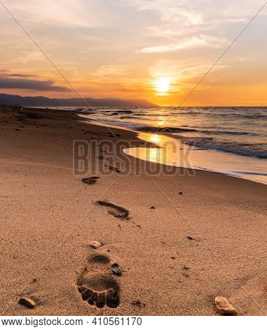 A Seascape With Footprints In The Sand In Vertical Format