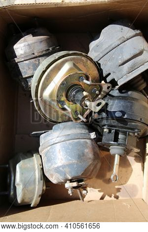 Old Car Parts. Brake Power Booster. brake master cylinder. Recycling of old Auto Parts. Old Used Metal Car Parts in a Cardboard Box for recycling. worn out metal parts.